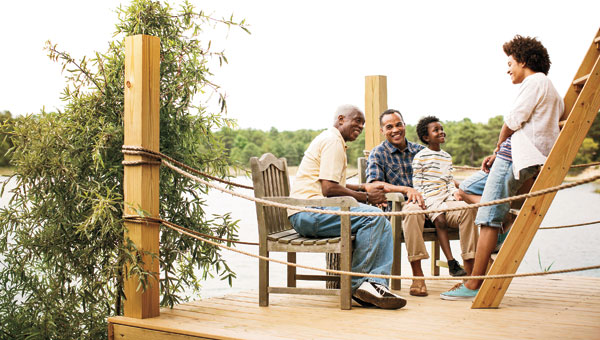 An image of a family sitting together on a dock near a river