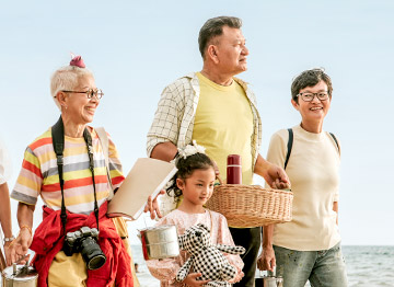 Article Image - 3 generations of family walking along the beach. Plan a family vacation without breaking the bank