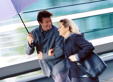 Article Image - A man and woman walking together under an umbrella. Explore how to prepare for 4 retirement risks.
