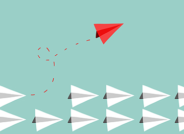 Article Image - One red paper airplane flying out of a double row of white paper airplanes.
