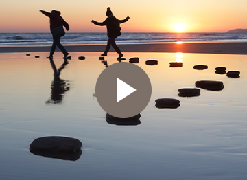 Article Image - Two people walking on a line of rocks on the beach