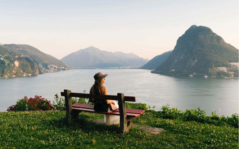 Image of a woman sitting on a bench near a lake and mountain